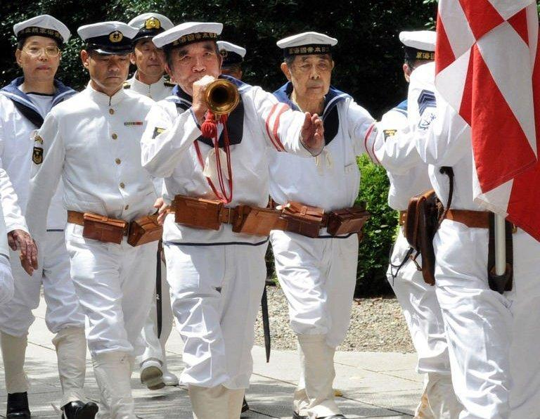 War veterans and others wearing uniforms of the Imperial Navy march at the Yasukuni shrine