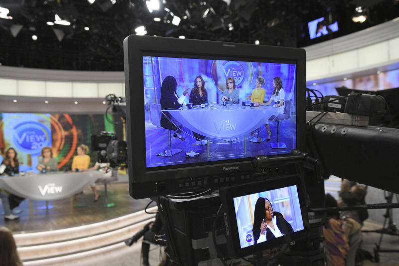 """In this March 21, 2017 photo released by ABC, co-hosts, from left, Whoopi Goldberg, Sunny Hostin, Joy Behar, Sara Haines and Jedediah Bila appear on a monitor during a broadcast of """"The View,"""" in New York. The unquenchable thirst for chatter about President Donald Trump has changed the dynamics of a fierce daytime television competition much as it has in late-night TV. """"The View"""" has spent more time talking politics with the arrival of a new administration, stopping the momentum of its rival """"The Talk,"""" which sticks to pop culture. (Lorenzo Bevilaqua/ABC via AP)"""