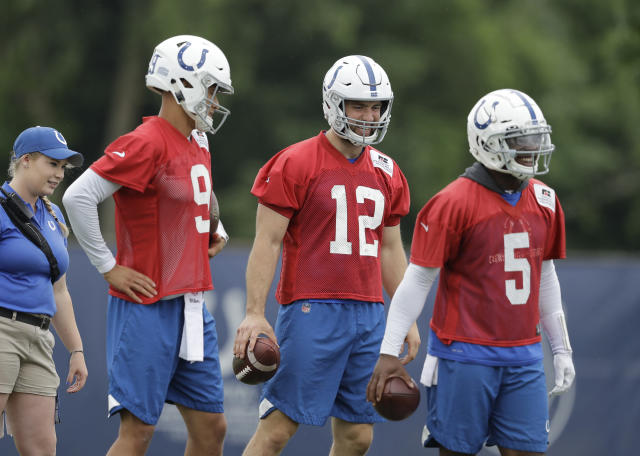 Indianapolis Colts quarterback Andrew Luck (12) waits to runs a drill with Brad Kaaya (9) and Phillip Walker (5) during practice at the NFL football team's training camp, Tuesday, June 12, 2018, in Indianapolis. (AP Photo/Darron Cummings)