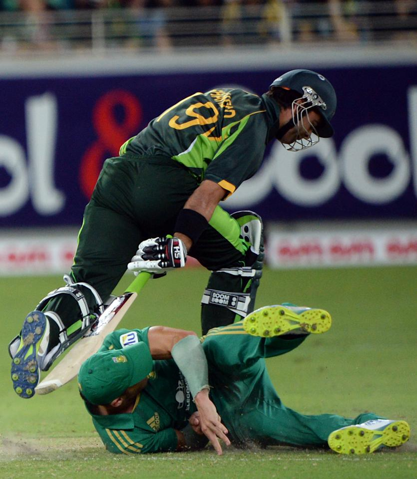 Pakistani batsman Ahmad Shezad collides with South African captain Faf du Plessis (ground) during the second and last cricket T20 International at Dubai stadium on November 15, 2013 in Dubai. South Africa sparked another Pakistan batting collapse to win the second Twenty20 international by six runs, taking the two-match series 2-0. AFP PHOTO/ Asif HASSAN        (Photo credit should read ASIF HASSAN/AFP/Getty Images)