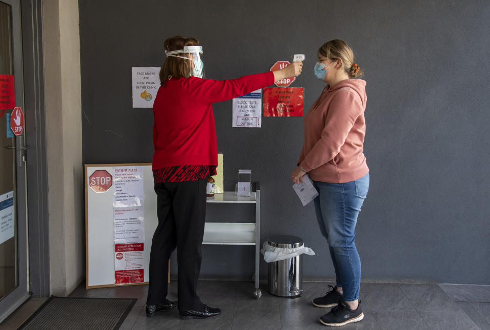 A patient has her temperature checked at a medical clinic during lockdown due to the continuing spread of the coronavirus in Melbourne, Thursday, Aug. 6, 2020. Victoria state, Australia's coronavirus hot spot, announced on Monday that businesses will be closed and scaled down in a bid to curb the spread of the virus. (AP Photo/Andy Brownbill)