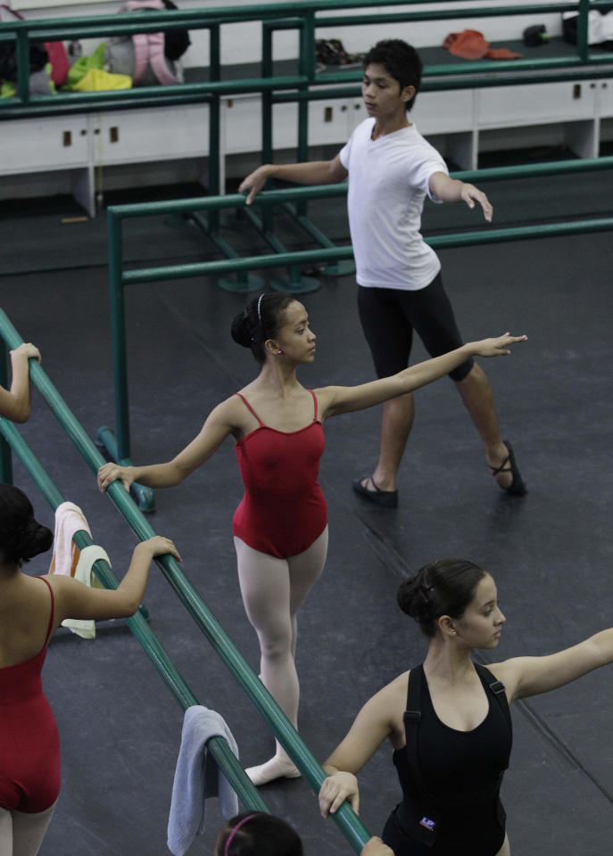 In this photo taken Nov. 25, 2012, Filipino slum dwellers Jessa Balote, center, and Jamil Montebon, top, practice with other students during a class at Ballet Manila at the Philippine capital. Aside from well-off students, the school picks scholars among kids living in slum areas of Manila and enroll them at their dance scholarship program where they are given a monthly stipend. (AP Photo/Aaron Favila)