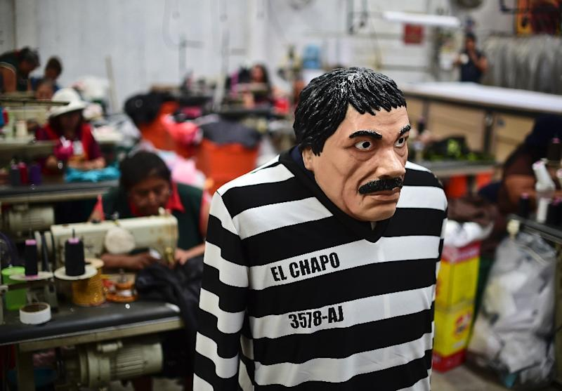 """A costume and a mask representing Mexican drug trafficker Joaquin """"El Chapo"""" Guzman, are displayed at a costume and mask factory on October 16, 2015, in Jiutepec, Morelos State (AFP Photo/Ronaldo Schemidt)"""
