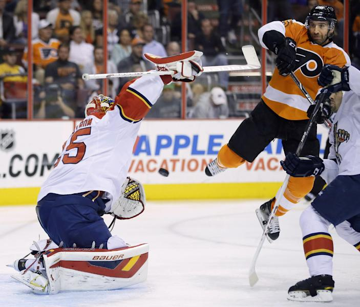 Florida Panthers' Jacob Markstrom, left, of Sweden, catches a shot as Philadelphia Flyers' Maxime Talbot leaps by during the second period of an NHL hockey game, Tuesday, Oct. 8, 2013, in Philadelphia. (AP Photo/Matt Slocum)