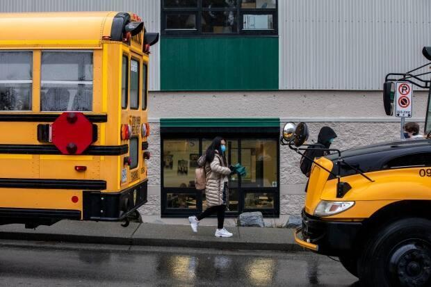 Students are pictured on a school bus after classes end at Earl Marriott Secondary School in Surrey, B.C., on Jan. 4, 2021. (Ben Nelms/CBC - image credit)