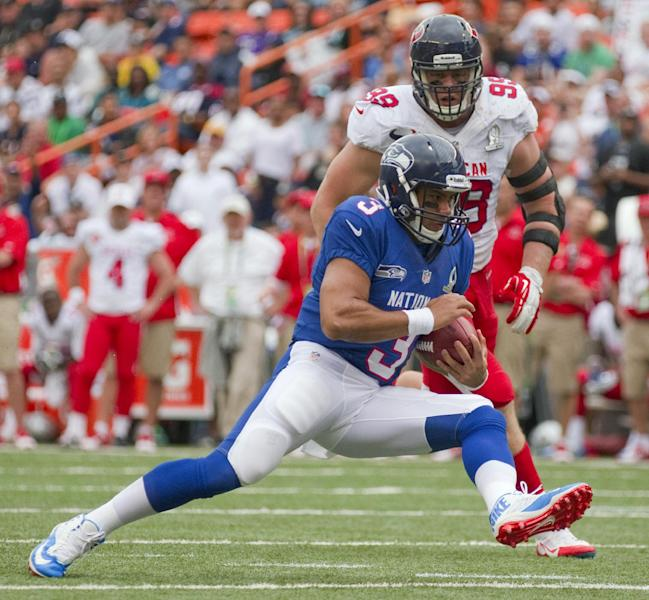 Houston Texans defensive end J.J. Watt (99) of the AFC attempts to chase down Seahawks quarterback Russell Wilson (3) of the NFC in the third quarter of the NFL Pro Bowl football game in Honolulu, Sunday, Jan. 27, 2013. (AP Photo/Eugene Tanner)