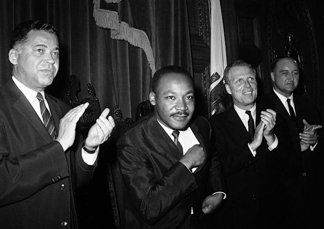<p>Dr. Martin Luther King Jr., as he sits down following his speech to the joint session of the Massachusetts Legislature in Boston, April 22, 1965. Applauding at left is Massachusetts Attorney Gen. Edward W. Brooke. King will lead a civil rights march to Boston Common. (AP Photo) </p>