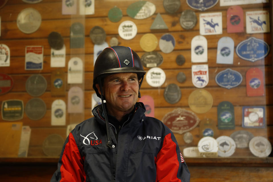 FILE - In this April 2, 2020, file photo, Phillip Dutton, a medal-winning equestrian on the U.S. Olympic team, smiles after a training session at his farm in West Grove, Pa. Older Olympians will be proving that age is just a number in Tokyo. The oldest member of Team USA headed to Tokyo is Dutton, a 57-year-old equestrian who competes in eventing, a combination of dressage, cross-country and jumping. (AP Photo/Matt Slocum, File)