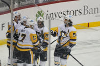 Pittsburgh Penguins center Sidney Crosby (87), and teammates celebrate with right wing Bryan Rust (17) after he scored a goal during the second period of an NHL hockey game against the New Jersey Devils, Sunday, April 11, 2021, in Newark, N.J. (AP Photo/Kathy Willens)