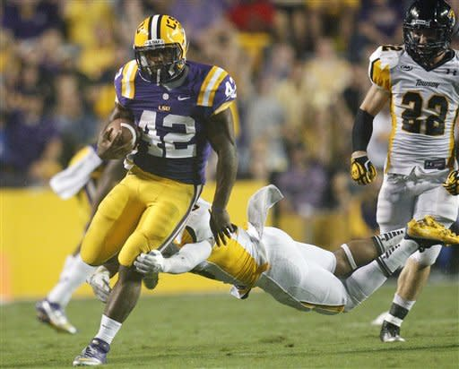 LSU running back Michael Ford (42) runs away from Towson safety Jordan Dangerfield, as another defender trails during the second half of an NCAA college football game in Baton Rouge, La., Saturday, Sept. 29, 2012. (AP Photo/Bill Haber)