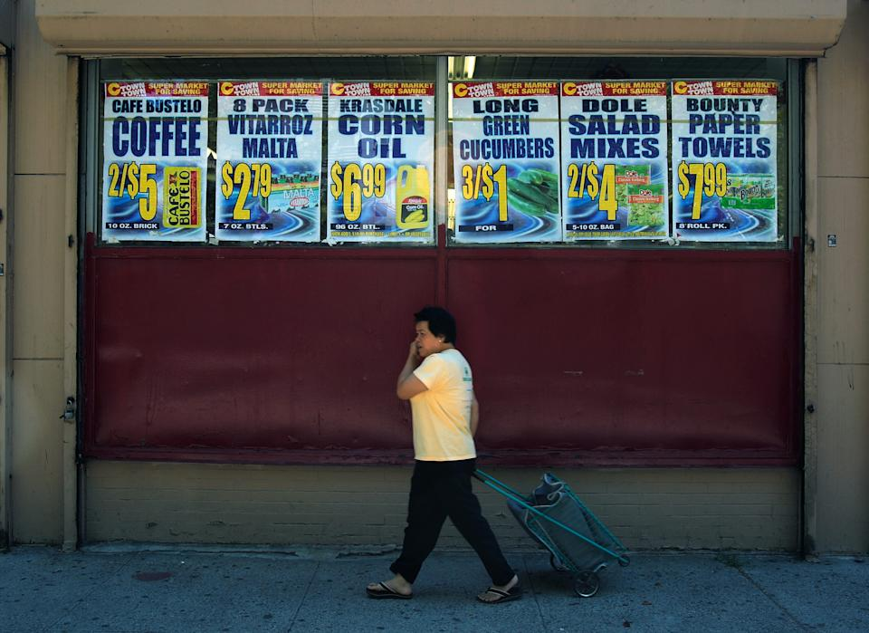 A woman walks past advertised prices at a grocery store in Manhattan