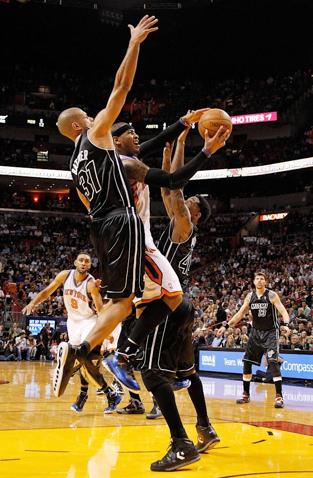 MIAMI, FL - FEBRUARY 23: Carmelo Anthony #7 of the New York Knicks shoots over Shane Battier #31 and Udonis Haslem #40 of the Miami Heat during a game at American Airlines Arena on February 23, 2012 in Miami, Florida. NOTE TO USER: User expressly acknowledges and agrees that, by downloading and/or using this Photograph, User is consenting to the terms and conditions of the Getty Images License Agreement. (Photo by Mike Ehrmann/Getty Images)
