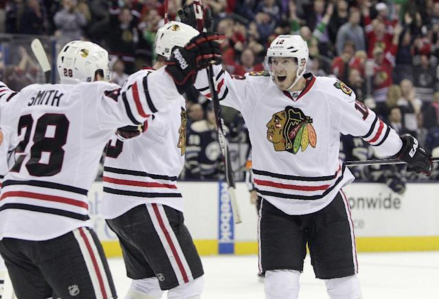 Chicago Blackhawks' Peter Regin, right, of Denmark, celebrates their goal against the Columbus Blue Jackets with teammates Ben Smith, left, and Bryan Bickell during the third period of an NHL hockey game on Friday, April 4, 2014, in Columbus, Ohio. The Blackhawks defeated the Blue Jackets 4-3. (AP Photo/Jay LaPrete)