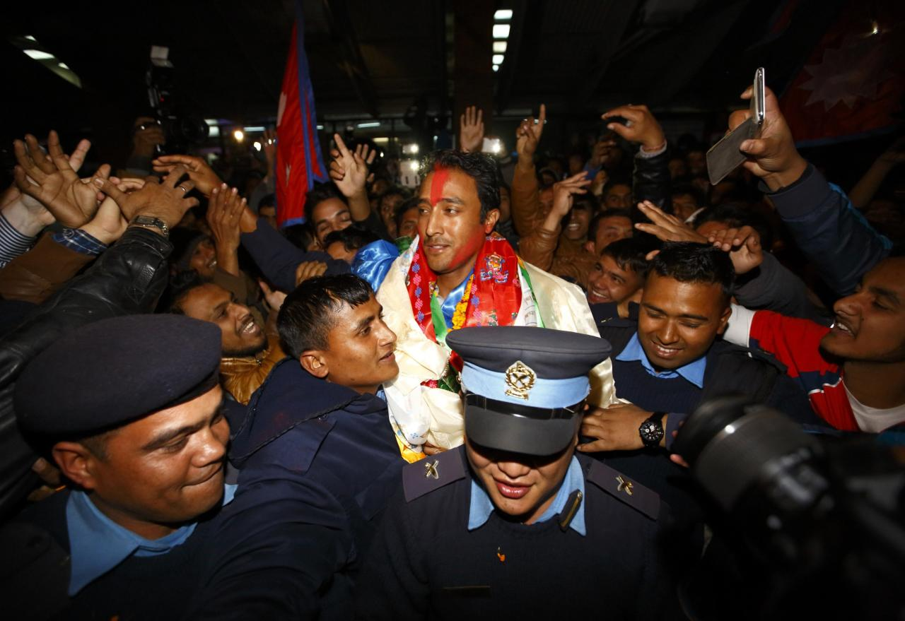 Captain of Nepali national cricket team Paras Khadka (C) is given a hero's welcome by Nepali supporters upon the team's arrival at the airport after qualifying for the first time in ICC World Twenty20 cricket in Bangladesh next year in Kathmandu December 1, 2013. The Nepali cricket team achieved a historic success and qualified for the World Twenty20 Cricket after the team managed to secure third place in the ICC World T20 Qualifiers in the UAE. REUTERS/Navesh Chitrakar (NEPAL - Tags: SPORT CRICKET)
