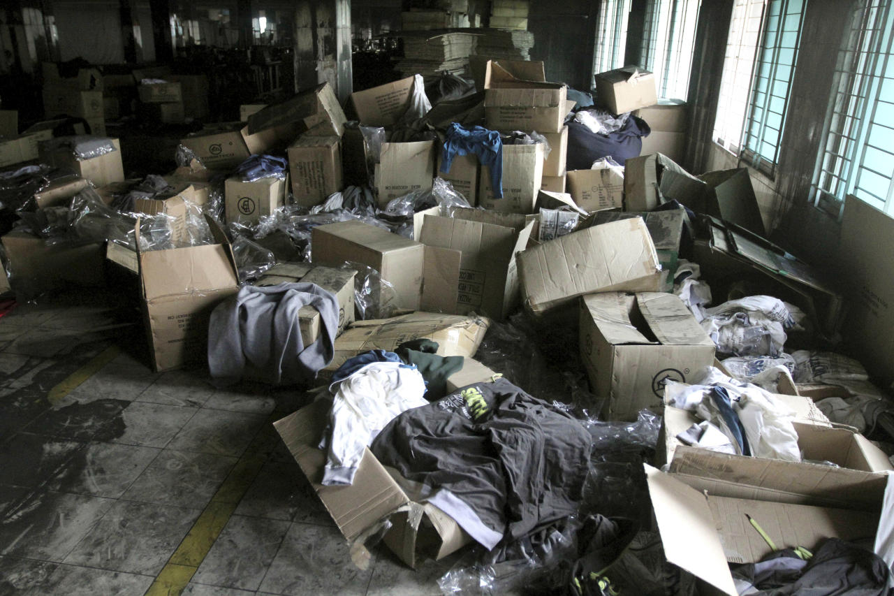 Boxes of garments lay near equipment charred in the fire that killed 112 workers Saturday at the Tazreen Fashions Ltd. factory,on the outskirts of Dhaha, Bangladesh, Wednesday, Nov. 28, 2012. Garments and documents left behind in the factory show it was used by a host of major American and European retailers, though at least one of them — Wal-Mart — had been aware of safety problems. Wal-Mart blames a supplier for using Tazreen Fashions without its knowledge. (AP Photo/Ashraful Alam Tito)