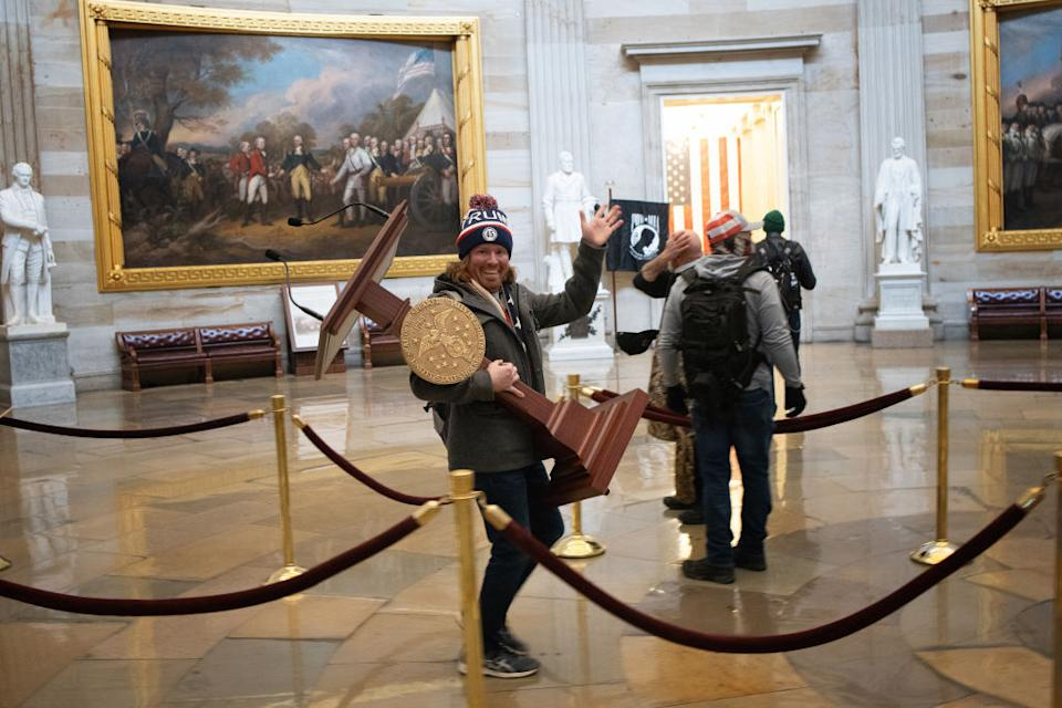 A pro-Trump protester carries the lectern of US Speaker of the House Nancy Pelosi after the mob ransacked the building as security looked on. Source: Getty