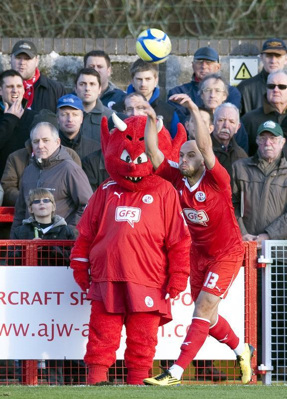 "Crawley Town's David Hunt (R) takes a throw-on in front of of the team mascot against Bristol City during the FA Cup third round football match at Broadfield Stadium in Crawley on January 7, 2012. Crawley Town won the game 1-0 and advance to the fourth round of the FA cup. AFP PHOTO / ADRIAN DENNIS RESTRICTED TO EDITORIAL USE. No use with unauthorized audio, video, data, fixture lists, club/league logos or ""live"" services. Online in-match use limited to 45 images, no video emulation. No use in betting, games or single club/league/player publications"