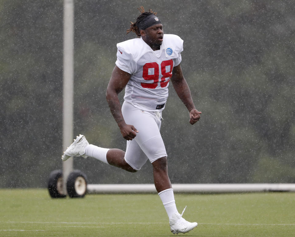 FILE - In this Aug. 2, 2018, file photo, Atlanta Falcons defensive end Takkarist McKinley (98) runs in the rain during NFL football training camp in Flowery Branch, Ga. McKinley, the Falcons' first-round pick in 2017, showed his disruptive potential when he recorded six sacks as a rookie. But the outside linebacker has had surgeries on both shoulders the last two years and he's being watched closely in training camp. (AP Photo/John Bazemore, File)