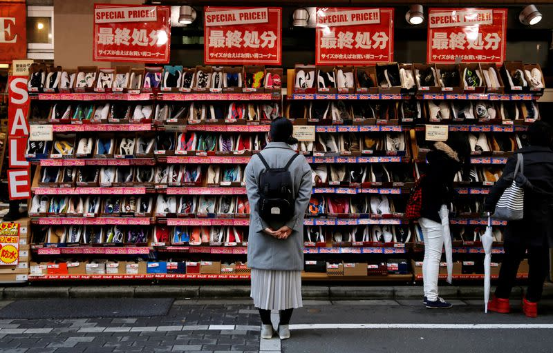Japan keeps view economy recovering, flags virus as big risk