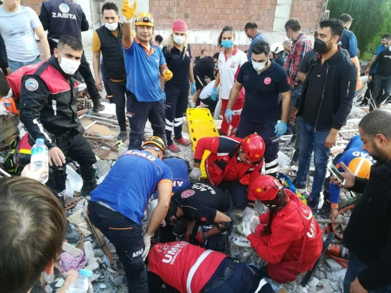 Rescuers search for survivors at a collapsed building in Izmir