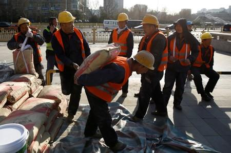 FILE PHOTO: A builder carries a sack of cement in central Beijing