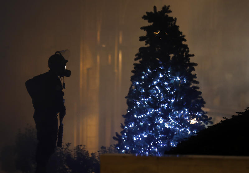 A riot police officer stands next of a Christmas tree during a protest where some anti-government protesters try to enter parliament square in downtown Beirut, Lebanon, Saturday, Dec. 14, 2019. The recent clashes marked some of the worst in the capital since demonstrations began two months ago. The rise in tensions comes as politicians have failed to agree on forming a new government. (AP Photo/Hussein Malla)
