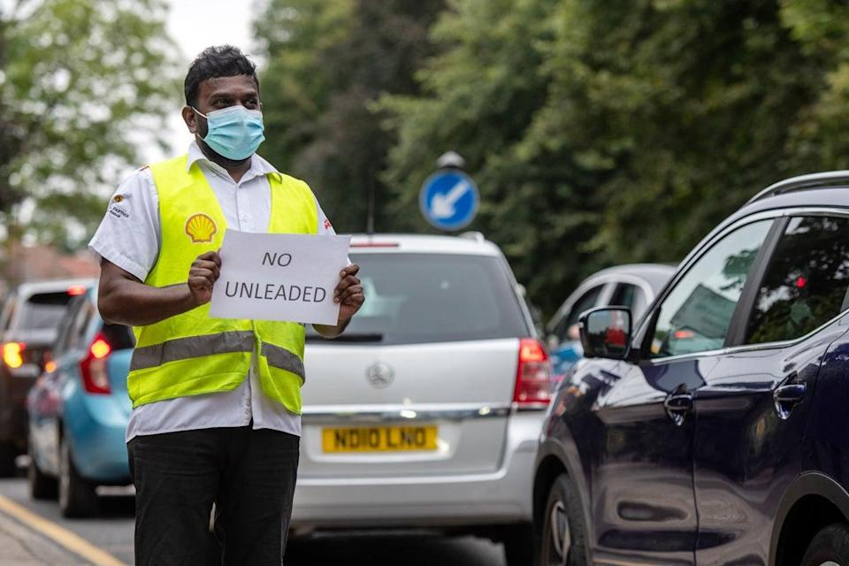 A Shell garage employee holds a sign on the side of the road informing a queue of traffic that they do not have unleaded petrol (Getty)