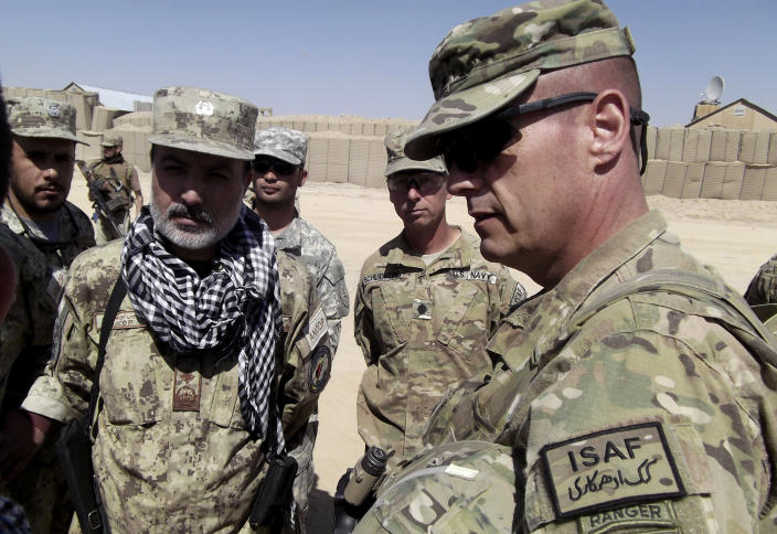 This photo taken Oct. 10, 2012 shows U.S. Brig. Gen. John Charlton, right, talking with Afghan National Civil Order Police (ANCOP) brigade commander Gul Mohammed Rasikh at the U.S base in An Band district, Ghazni province, Afghanistan. Fed up with the Taliban closing their schools and committing other acts of oppression, men in a village about 100 miles south of Kabul took up arms late last spring and chased out the insurgents with no help from the Afghan government or U.S. military. Small-scale revolts like the one in the village of Kunsaf, Ghazni, in recent months indicate bits of a do-it-yourself anti-insurgency that the U.S. hopes Afghan authorities can transform into a wider movement that could undercut the Taliban in areas it still dominates after 11 years of war. (AP Photo/Robert Burns)