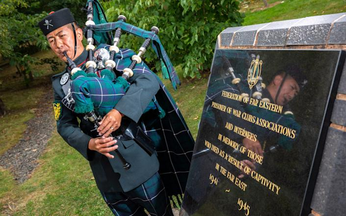 A lone piper plays at the VJ Day commemorations - PA