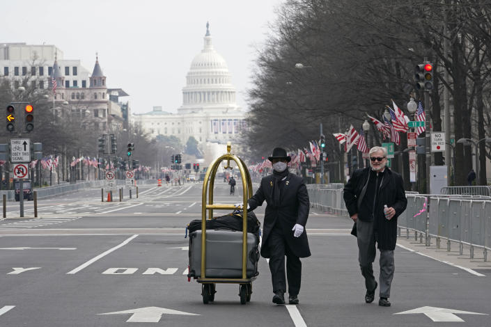 Danish Rozario, left, of Silver Spring, Md., wheels the baggage down Pennsylvania Avenue for a guest at the Trump Hotel in Washington, Friday, Jan. 15, 2021, ahead of the inauguration of President-elect Joe Biden and Vice President-elect Kamala Harris.Between the still-raging pandemic and suddenly very real threat of violence from supporters of outgoing President Donald Trump, Jan. 20 promises to be one of the most unusual presidential inaugurations in American history. Joe Biden and Kamala Harris will take the oath of office outside the Capitol. (AP Photo/Susan Walsh)