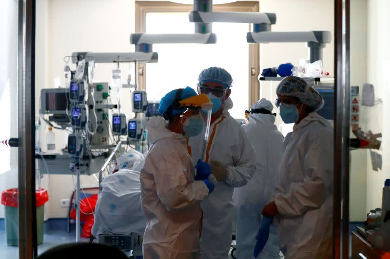Medical workers talk before taking care of a patient infected with COVID-19 at the intensive care unit (ICU) of Ramon y Cajal hospital in Madrid