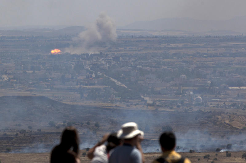 Israelis and tourists look at fire caused by fighting in Syria from an observation point on Mt. Bental in the Golan Heights, near the border between the Israeli-controlled Golan Heights and Syria, Friday, June 7, 2013. Syrian rebels on Thursday briefly captured a crossing point along a cease-fire line with Israel in the contested Golan Heights. (AP Photo/Sebastian Scheiner)