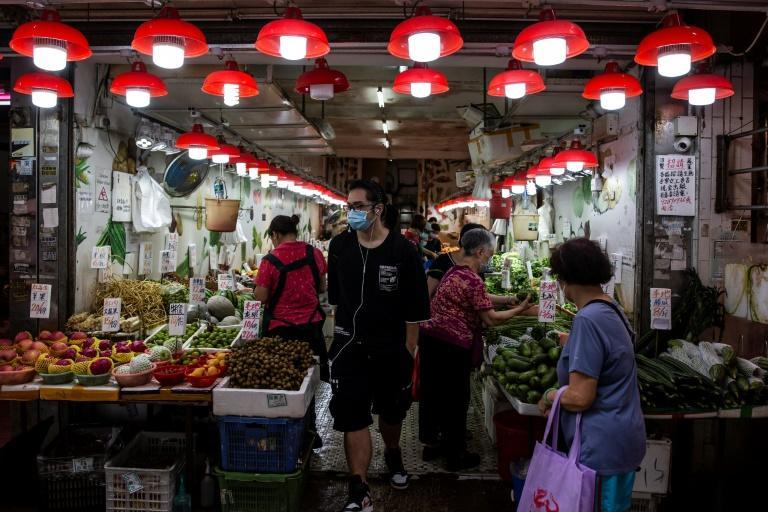 People shop at a fruit and vegetable store in Hong Kong