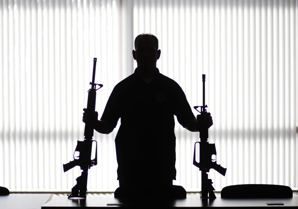 """FILE - In this Aug. 29, 2017, file photo, an ATF agent poses with homemade rifles, or """"ghost guns,"""" at an ATF field office in Glendale, Calif. California's attorney general is suing the Trump administration in an effort to crack down on so-called """"ghost guns"""" that can be built from parts with little ability to track or regulate the owner. (AP Photo/Jae C. Hong, File)"""