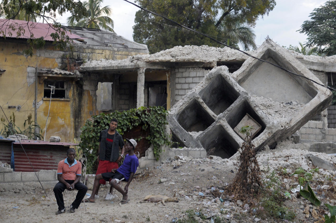 People sit outside a house that was destroyed by the January 2010 earthquake in Port au Prince January 3, 2012.  January 12th will mark the second anniversary of the devastating earthquake that killed more than 200,000 people.  Rubble removal remains a priority in the reconstruction effort. REUTERS/Swoan Parker (HAITI - Tags: DISASTER)