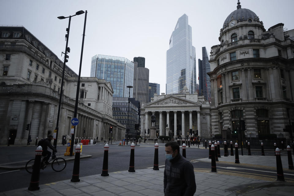 A man wearing a face mask to curb the spread of coronavirus walks backdropped by the Bank of England, left, and the Royal Exchange, centre, in the City of London financial district in London, Jan. 5, 2021, on the first morning of England entering a third national lockdown since the coronavirus outbreak began. British Prime Minister Boris Johnson on Monday night announced a tough new stay-at-home order that will last at least six weeks, as authorities struggle to stem a surge in COVID-19 infections that threatens to overwhelm hospitals around the U.K. (AP Photo/Matt Dunham)