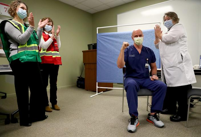 Dr. Steven Roumpf pumps his fist after receiving the COVID-19 vaccine from Mary Kay Foster, special pathogens program manager, on Dec. 16 at IU Health Neuroscience Center in Indianapolis. The hospital administered the first doses of the COVID-19 vaccine to medical workers.