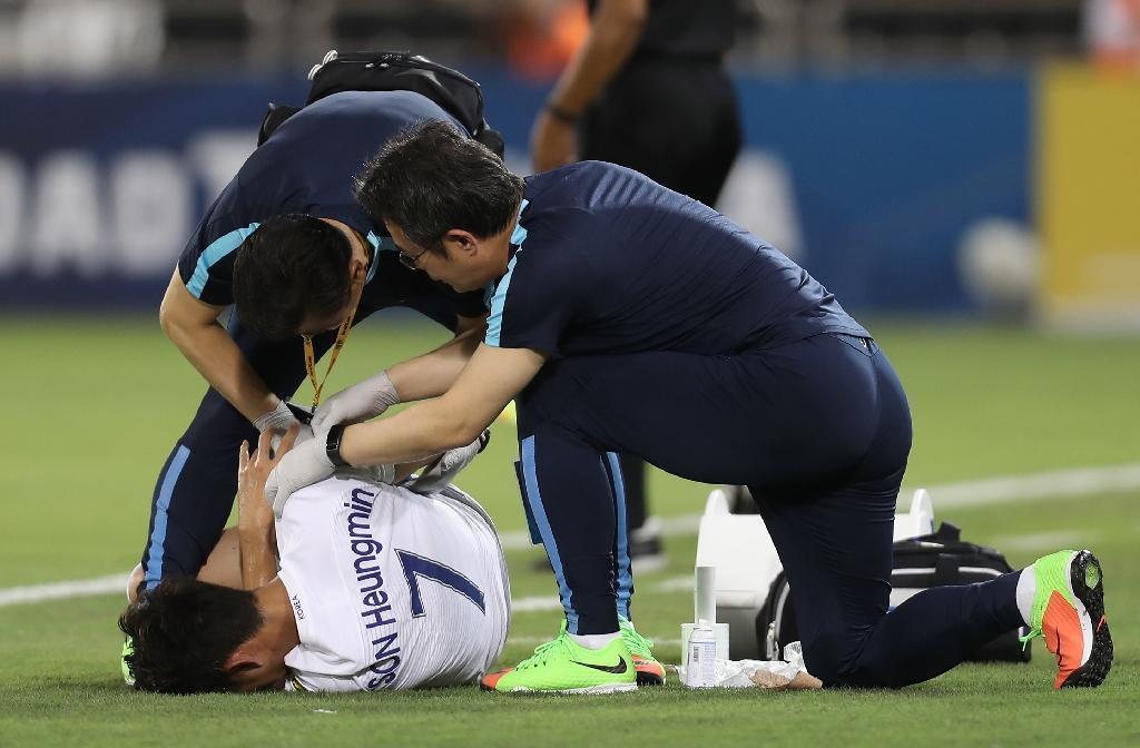 Son Heung-min leaves the field in obvious pain in the 33rd minute of South Korea's 3-2 World Cup qualifying defeat to Qatar, clutching his right forearm after an aerial challenge (AFP Photo/KARIM JAAFAR)