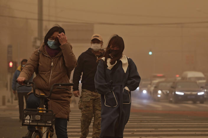 People wearing face masks walk across a street as capital city is hit by polluted air and sandstorm in Beijing, Monday, March 15, 2021. The sandstorm brought a tinted haze to Beijing's skies and sent air quality indices soaring on Monday. (AP Photo/Andy Wong)