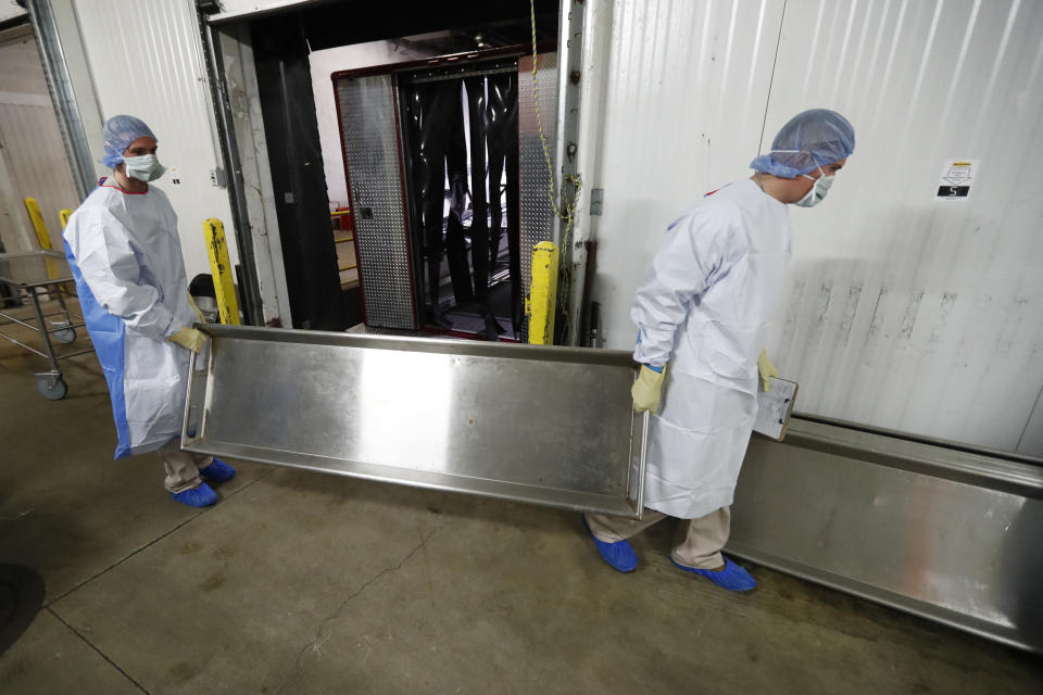 In this Tuesday, May 5, 2020, photo, Illinois National Guard members return a body tray to be sanitized on the loading dock at the Cook County Medical Examiner's auxiliary surge storage center after an emergency-management truck arrived with half-a-dozen bodies in Chicago. Incoming bodies to the surge center, with a capacity to hold 2,000 bodies, are taken to one of three rooms with the combined square footage of a football field. (AP Photo/Charles Rex Arbogast)