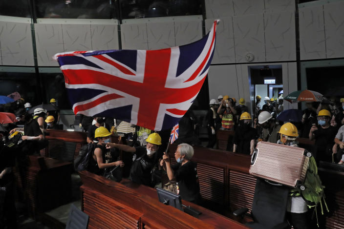 In this Monday, July 1, 2019, photo, Alexandra Wong, 63, carries the British flag as she joins other protesters who stormed the Legislative Council building in Hong Kong. Protesters smashed glass windows, sprayed rude graffiti and defaced Hong Kong's official emblem with black paint. But of all the dramatic photos showing hundreds of young protesters storming the city's parliament this week, one image makes for particularly uncomfortable viewing in Beijing: The British colonial flag draped aloft a podium in parliament's chamber. (AP Photo/Kin Cheung)