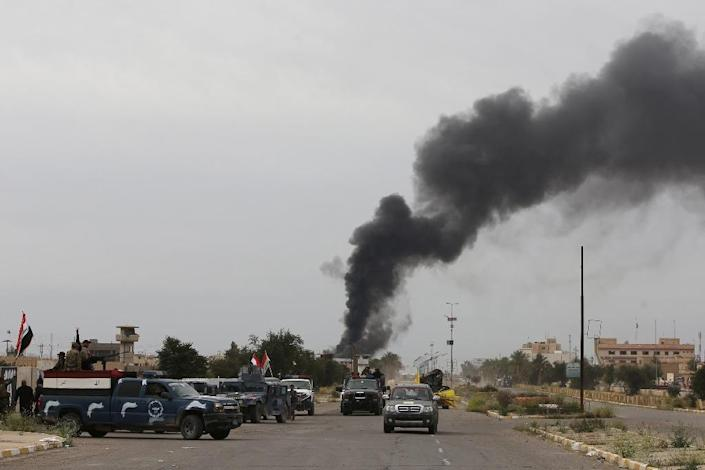Smoke rises from buildings as Iraqi security forces patrol a street in Tikrit, on April 1, 2015 (AFP Photo/Ahmad al-Rubaye)