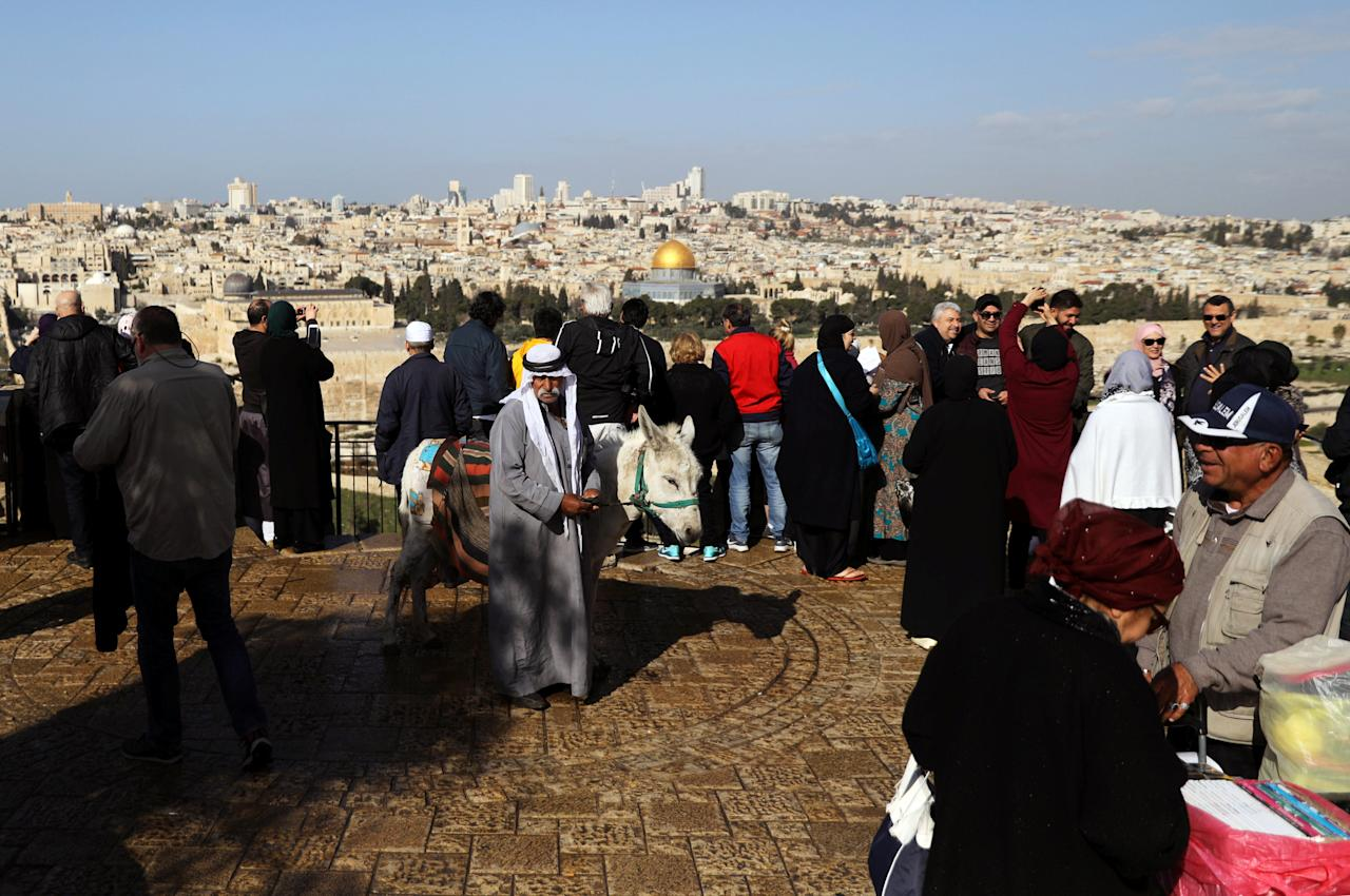 A man walks a donkey as tourists take photos in an observation point on Mount of Olives overlooking Jerusalem's Old City, February 22, 2018. REUTERS/Ammar Awad