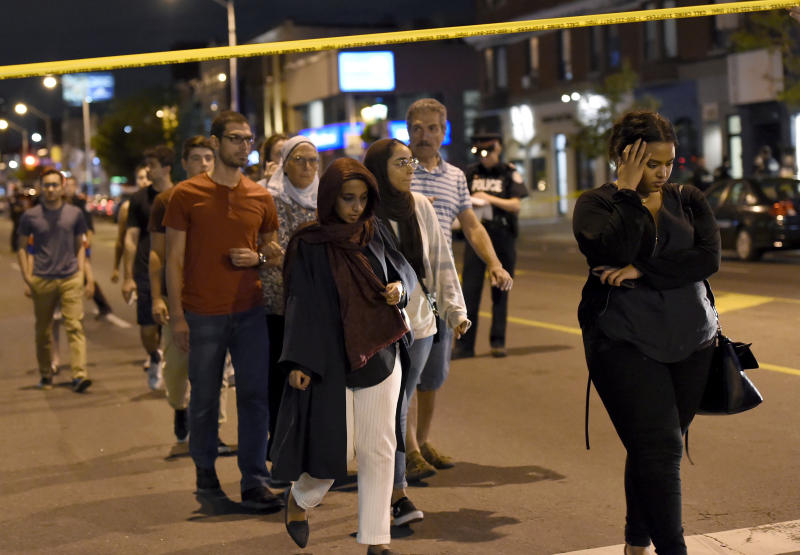 Civilians are escorted from the scene of a shooting in Toronto on Sunday, July 22, 2018. (Nathan Denette/The Canadian Press via AP)