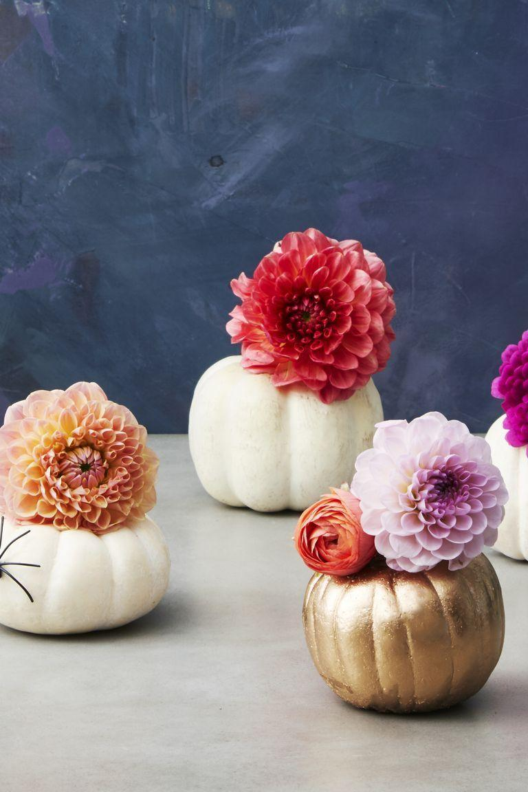 <p>Ditch the kitschy Halloween decor for a sophisticated centerpiece, like mini gourds that can double as vases. Fill carved pumpkins with water bottles (cut the bottoms off) and add ranunculuses, mums and dahlias. </p>