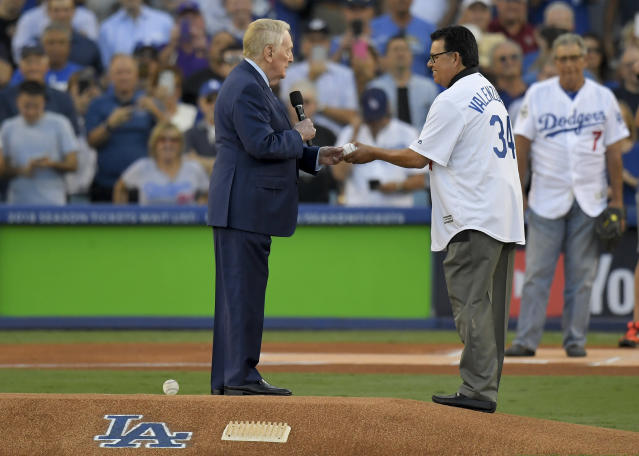 Fernando Valenzuela takes the first-ball from Vin Scully before Game 2 of the World Series at Dodger Stadium. (AP)