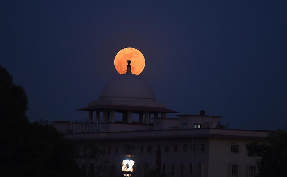 """<p>NEW DELHI, INDIA - MAY 26: A full """"Super blood moon"""" seen from around india Gate on May 26, 2021 in New Delhi, India. The first total lunar eclipse in two years is set to take place on May 26 and it will be a Super blood moon. It will also be visible from some parts of the Pacific, the Atlantic, and the Indian ocean. This is a Super Blood Moon, where the moon appears reddish orange in colour and really big as well as it is a full moon and the satellite is closest to Earth. The eclipsed Moon is dimly illuminated by red-orange light left over from all of the sunsets and sunrises occurring around the world at that time. (Photo by Raj K Raj/Hindustan Times via Getty Images)</p>"""