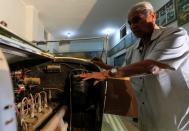 """Sayed Sima, a 70-years-old Egyptian collecting vintage cars checks the 120-year-old American automobile """"1900 Auburn"""" being in his store and his own exhibition of old cars in the Giza suburb of Abu Rawash"""