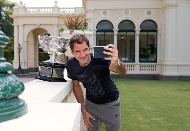 A supplied photo shows Switzerland's Roger Federer taking a selfie with the Australian Open Men's singles trophy during a visit to Government House in Melbourne, Australia, January 29, 2018. Fiona Hamilton/Tennis Australia/Handout via REUTERS ATTENTION EDITORS - THIS IMAGE WAS PROVIDED BY A THIRD PARTY. NO RESALES. NO ARCHIVE.