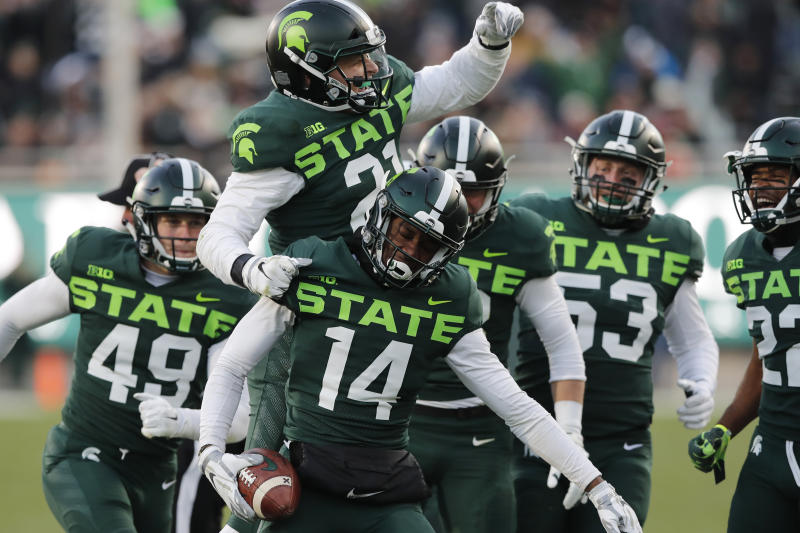 Michigan State linebacker Chase Kline (21) jumps on cornerback Davion Williams (14) after Williams' recovery of a fumble during the first half of an NCAA college football game against Illinois, Saturday, Nov. 9, 2019, in East Lansing, Mich. (AP Photo/Carlos Osorio)